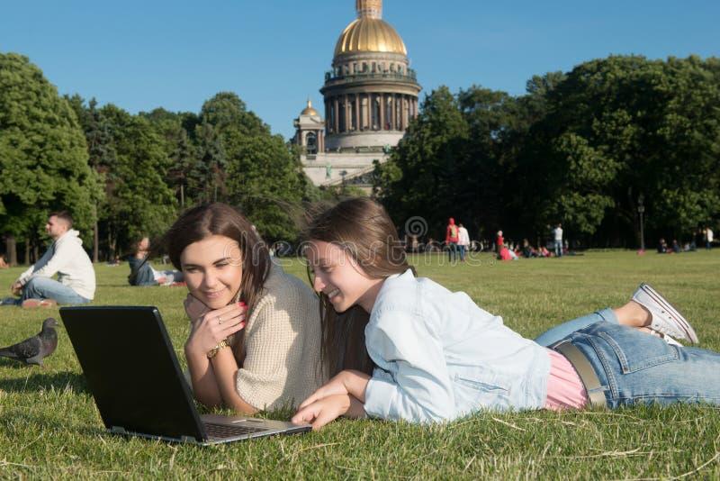 Duas meninas no parque com um portátil imagens de stock royalty free