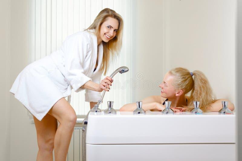 Duas meninas no salão de beleza dos termas fêmea em uma veste branca que guarda um chuveiro o louro da mulher toma procedimentos  fotos de stock