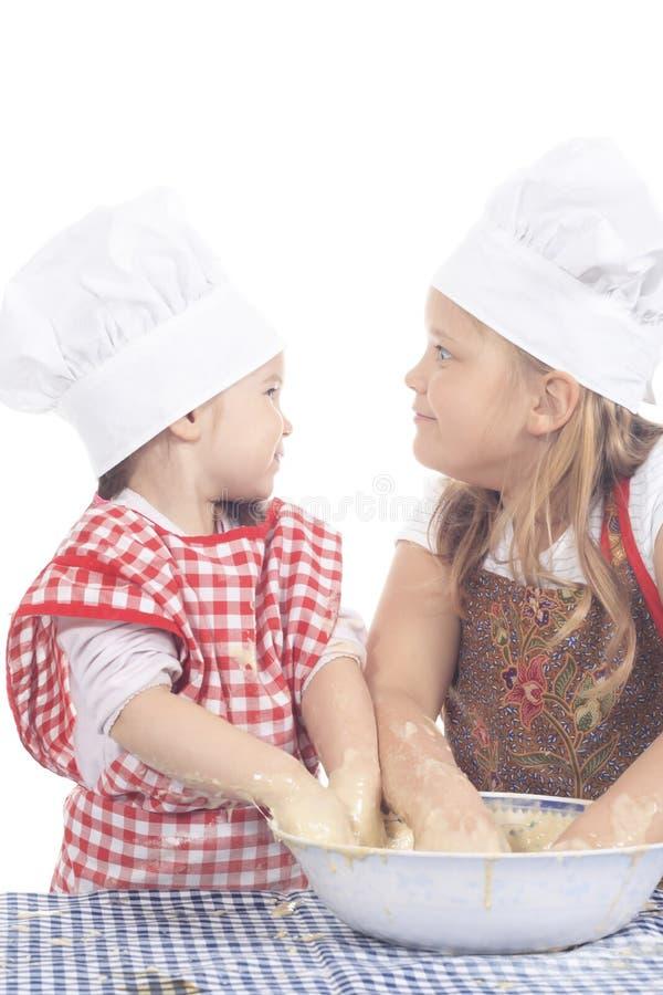 Duas meninas no traje do cozinheiro fotos de stock royalty free