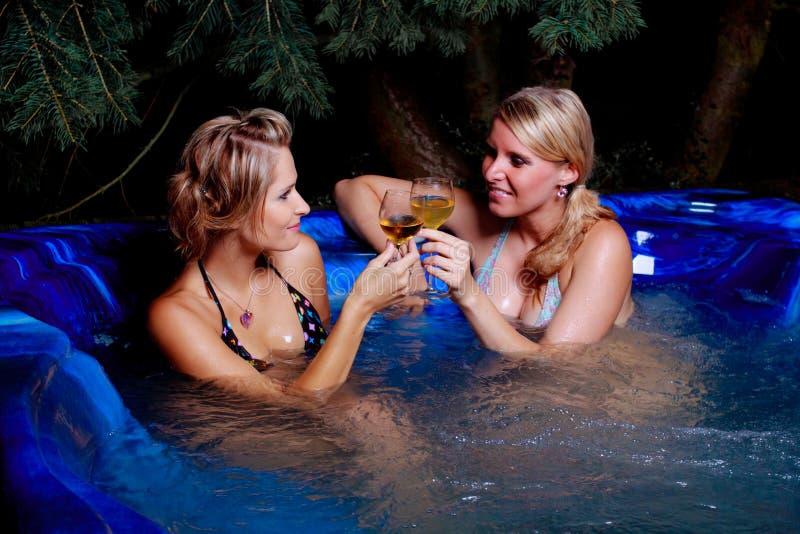 Duas meninas no whirlpool na noite imagens de stock royalty free