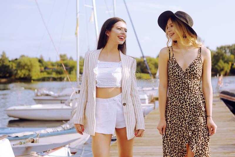 Duas meninas nos iate do fundo, barcos de navigação são sorrir, olhando a câmera Morena em um chapéu e um revestimento e um louro fotografia de stock royalty free