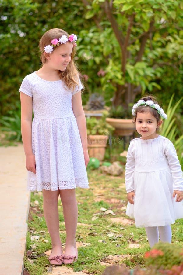 Duas meninas nos vestidos brancos e na grinalda da flor que tem o divertimento um jardim do ver?o fotografia de stock royalty free