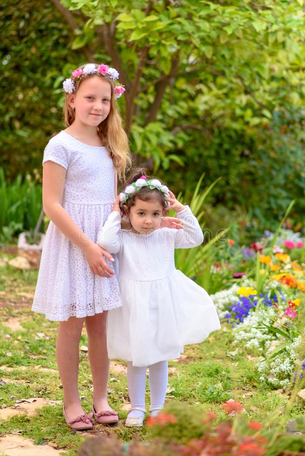 Duas meninas nos vestidos brancos e na grinalda da flor que tem o divertimento um jardim do ver?o imagens de stock