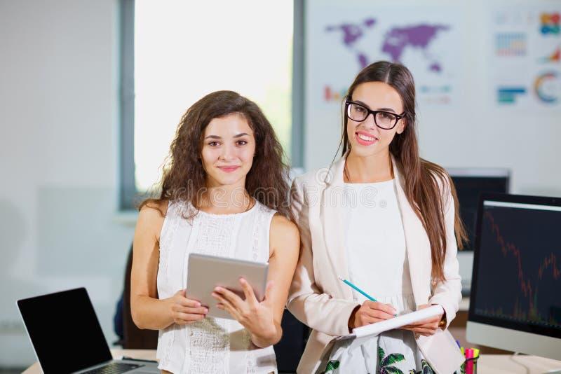 Duas meninas novas do negócio estão examinando originais e uma tabuleta imagem de stock
