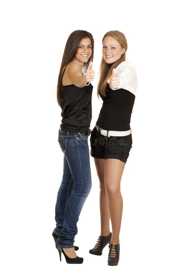 Duas meninas pegararam os polegares acima imagem de stock royalty free