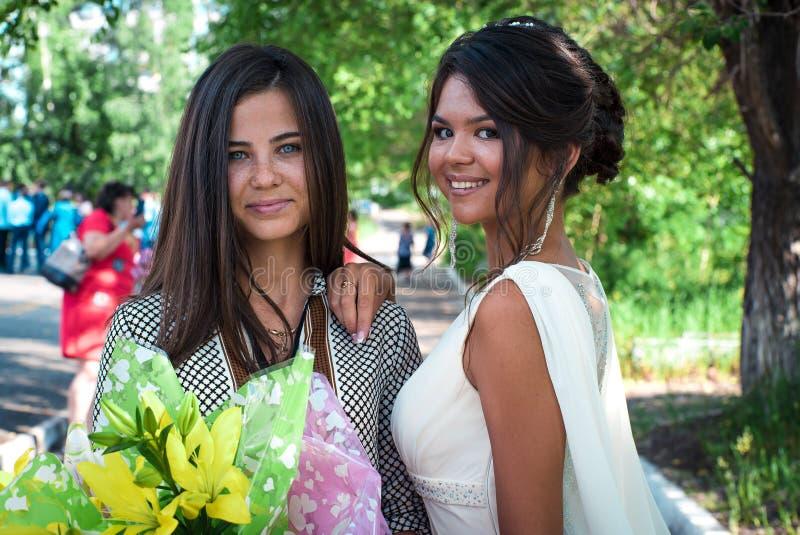 Duas meninas perto de uma árvore O retrato de uma senhora elegante bonita nova está levantando com flores A beleza das mulheres g foto de stock