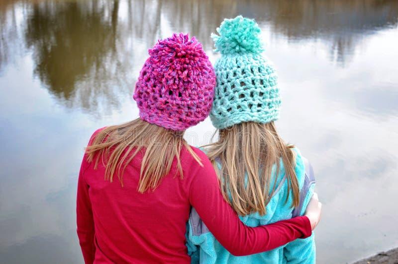 Duas meninas que abraçam com chapéus feitos crochê fotografia de stock royalty free