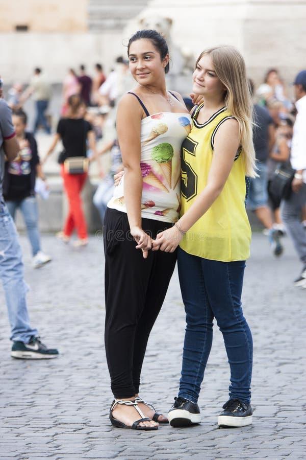 Duas meninas que abraçam e que guardam as mãos imagens de stock