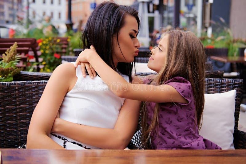 Duas meninas que abraçam na tabela em um café do ar livre fotografia de stock