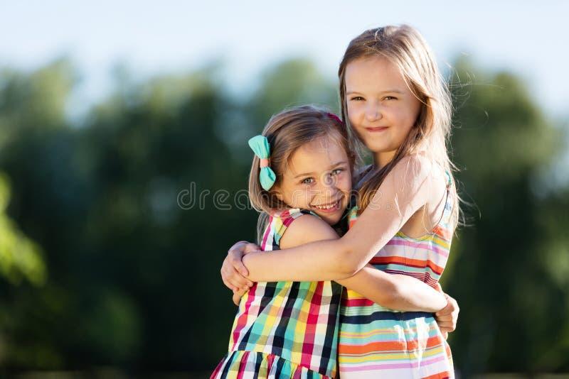 Duas meninas que abraçam-se no parque imagens de stock