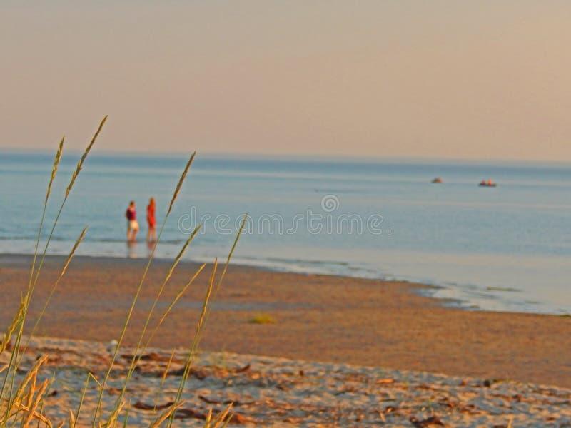 Duas meninas que andam ao longo do litoral do mar branco nos raios mornos do por do sol fotos de stock royalty free
