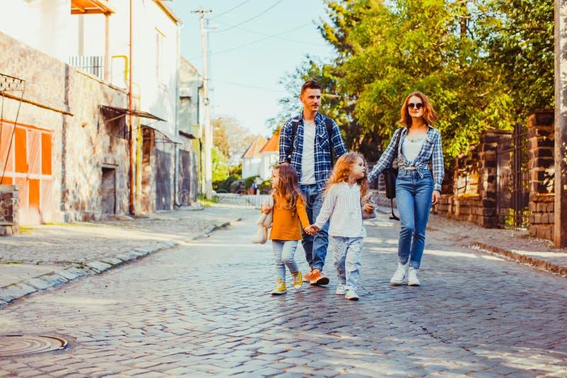 Duas meninas que andam com seus mãe e pai fotos de stock