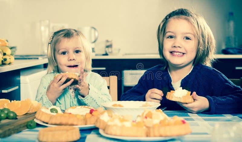 Duas meninas que apreciam a pastelaria com creme imagem de stock royalty free