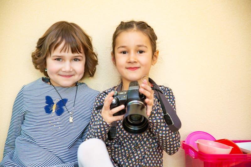 Duas meninas que aprendem como usar a câmera da foto fotografia de stock