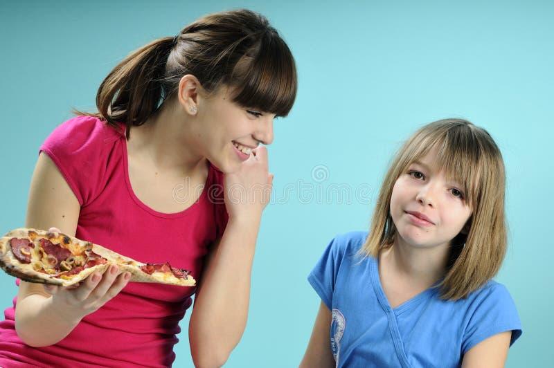 Duas meninas que comem a comida rápida foto de stock royalty free