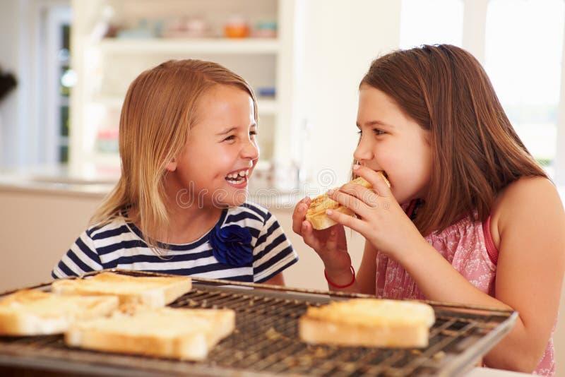 Duas meninas que comem o queijo no brinde na cozinha fotos de stock