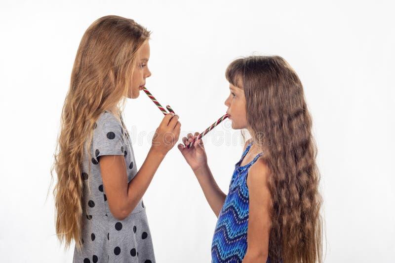 Duas meninas que comem um bastão deram forma a doces e giraas entre si imagens de stock
