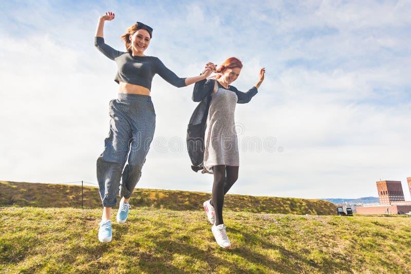 Duas meninas que correm abaixo de um monte em Oslo imagem de stock