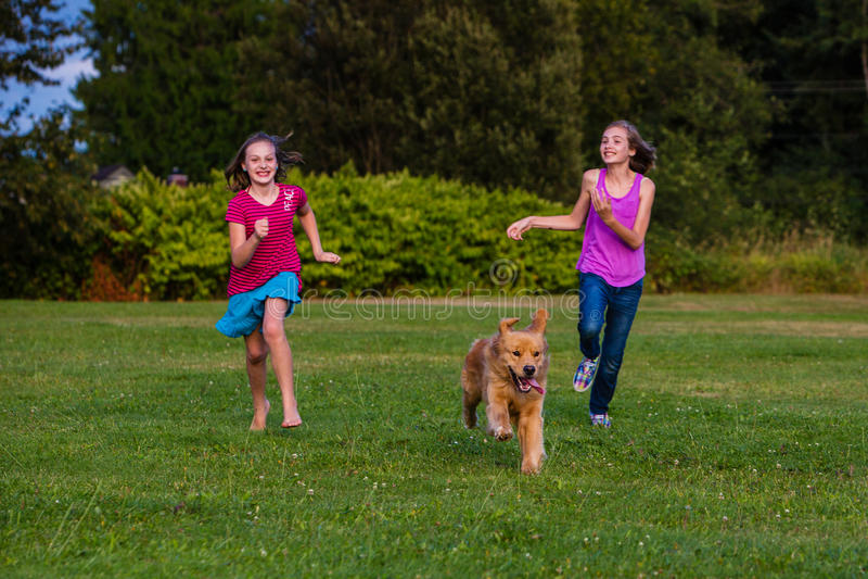 Duas meninas que correm com um cão fotografia de stock