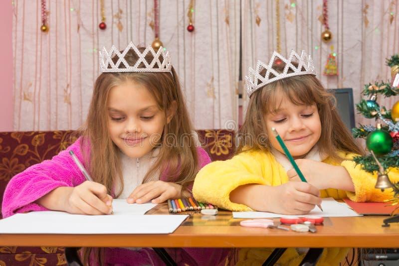 Duas meninas que escrevem felizmente a letra a Santa Claus que senta-se em uma mesa no ambiente familiar imagens de stock