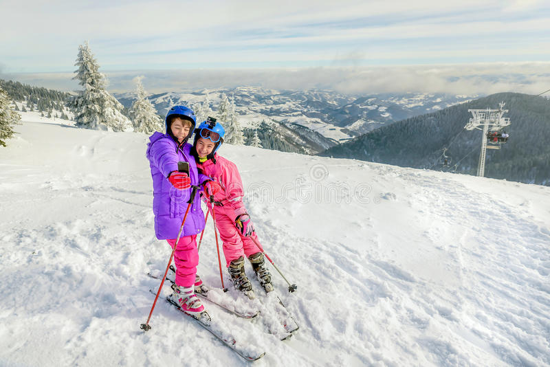 Duas meninas que estão com os skiis na parte superior do mountai nevado fotografia de stock royalty free