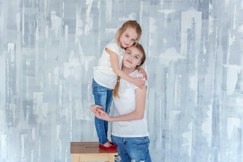 Duas meninas que estão na parede cinzenta imagens de stock royalty free