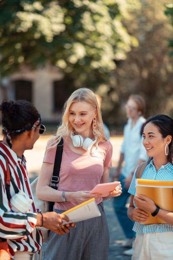 Duas meninas que falam com seu groupmate alegre foto de stock royalty free