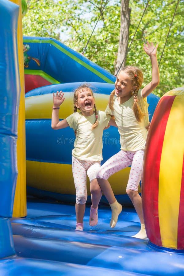 Duas meninas que fazem caretas felizmente saltando no trampolim inflável imagem de stock royalty free
