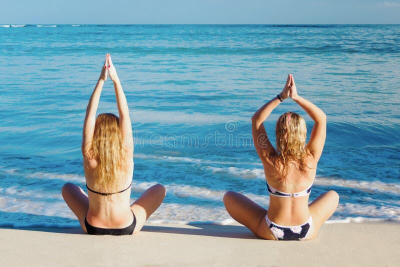Duas meninas que fazem a ioga levantam na costa do mar das caraíbas fotos de stock