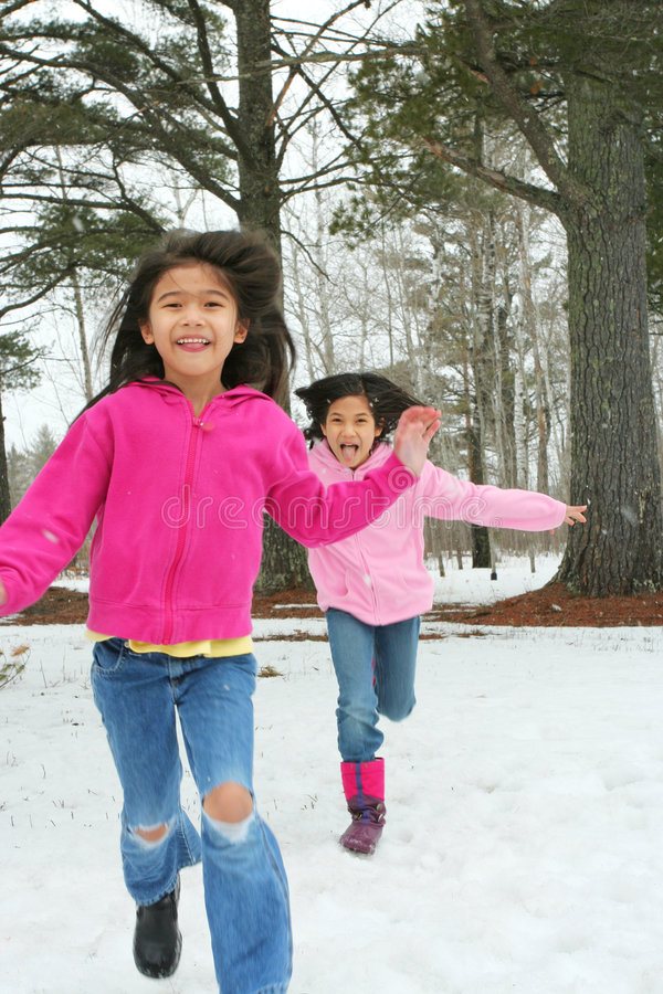 Duas meninas que funcionam através da neve foto de stock