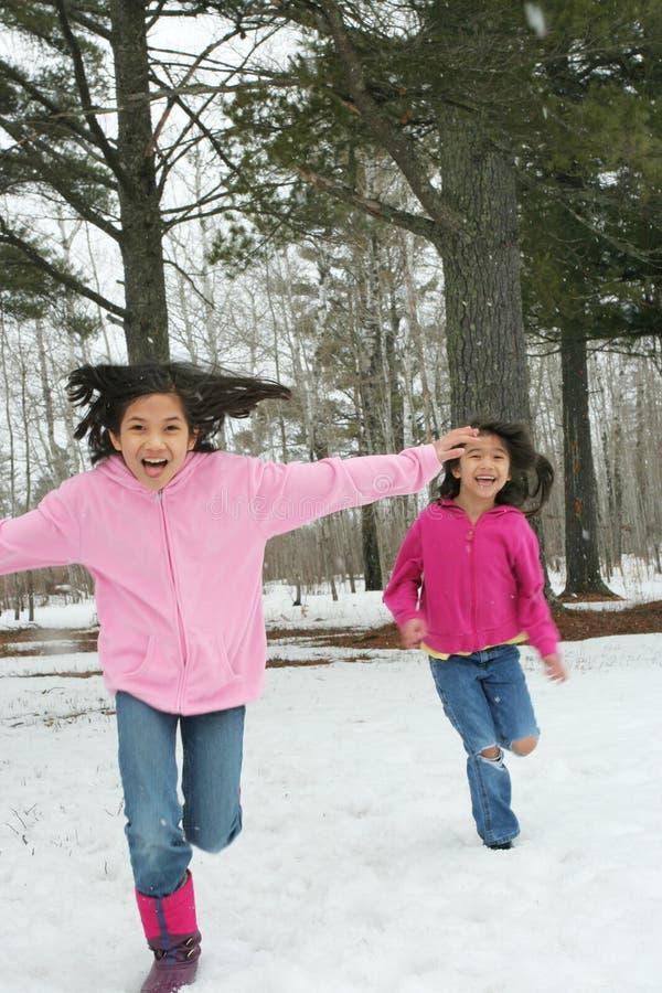 Duas meninas que funcionam através da neve imagem de stock