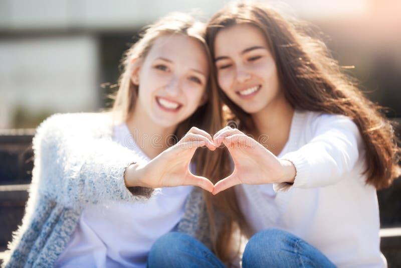 Duas meninas que guardam as mãos na forma do coração imagens de stock