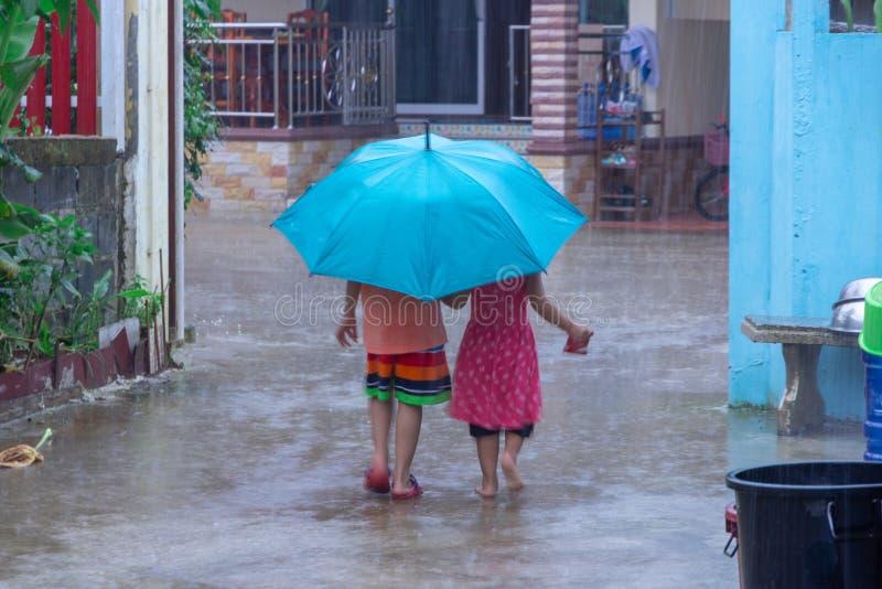 Duas meninas que guardam o guarda-chuva e que andam ao longo da rua a ho foto de stock royalty free