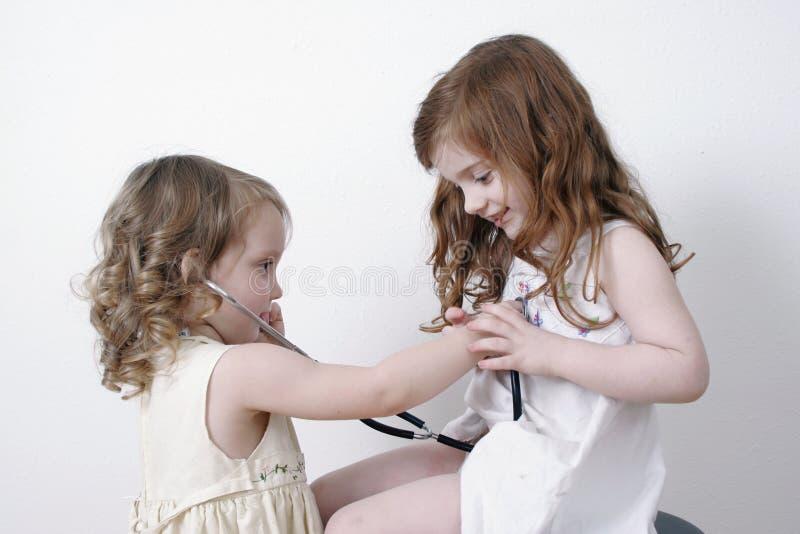 Duas meninas que jogam o doutor imagem de stock