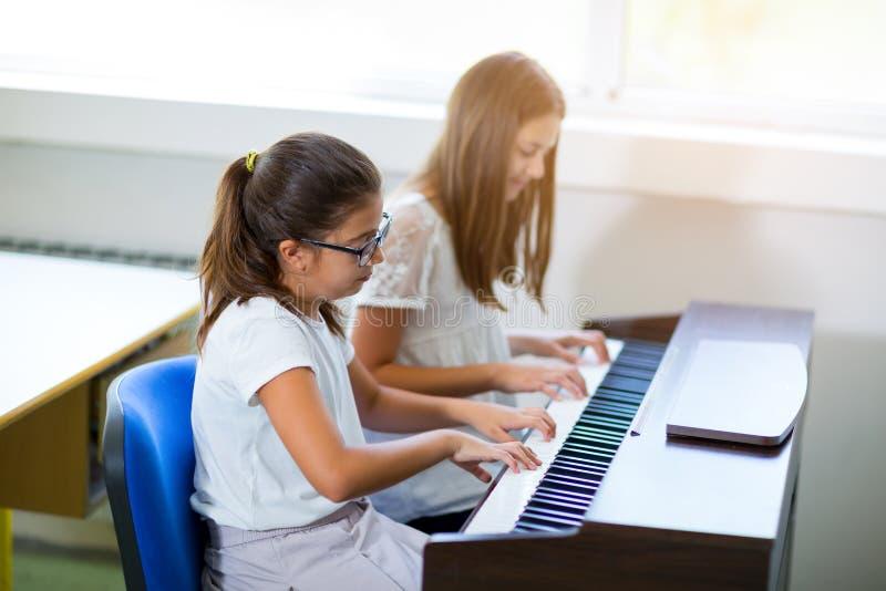 Duas meninas que jogam o piano na escola de música imagens de stock