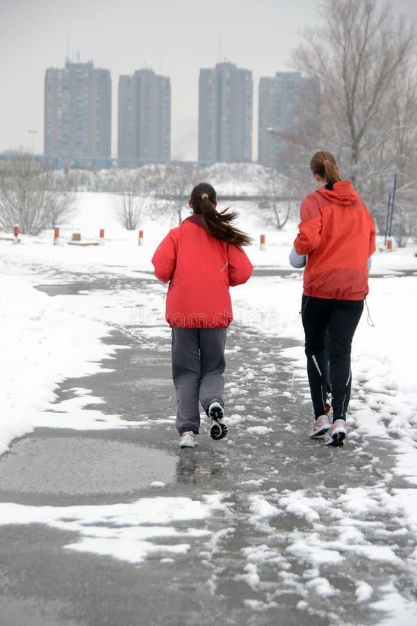 Duas meninas que movimentam-se na neve fotografia de stock