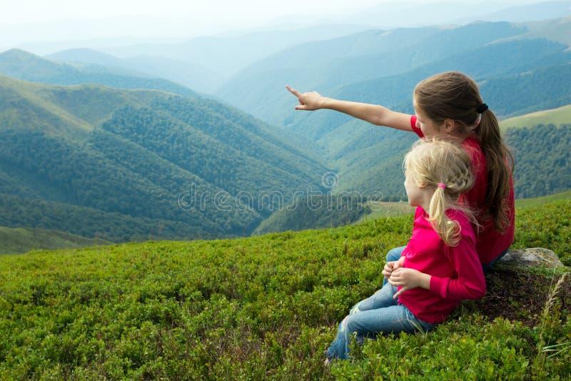Duas meninas que olham as montanhas fotografia de stock