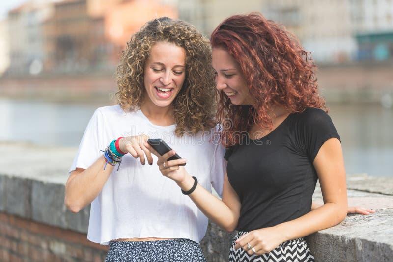 Duas meninas que olham o telefone esperto na cidade imagens de stock