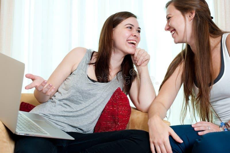 Duas meninas que olham uma parte superior do regaço. fotografia de stock