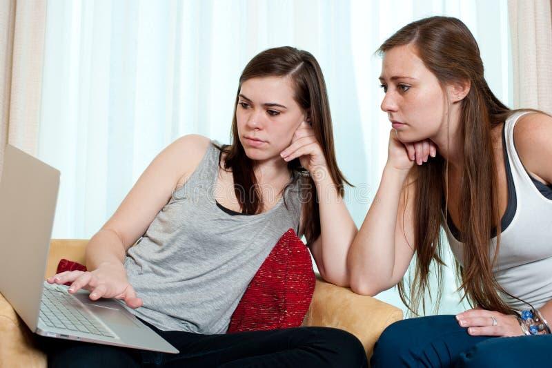 Duas meninas que olham uma parte superior do regaço. imagens de stock royalty free