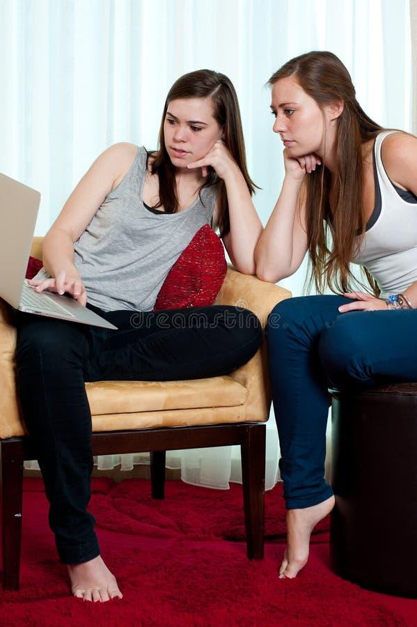 Duas meninas que olham uma parte superior do regaço. imagem de stock
