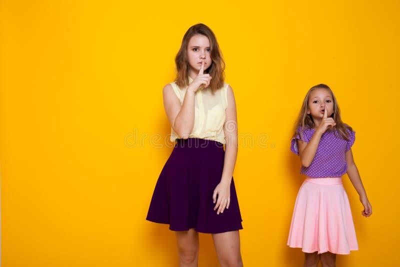 Duas meninas que pedem o silêncio com dedo mouth fotografia de stock royalty free