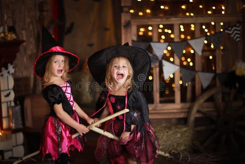 Duas meninas que riem a bruxa em um cabo de vassoura infância olá! imagem de stock