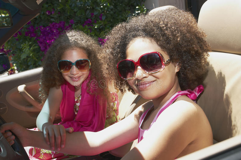 Duas meninas que sentam-se em um carro imagem de stock