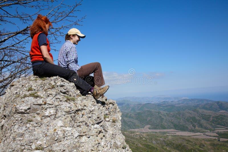Duas meninas que sentam-se em uma rocha imagens de stock royalty free