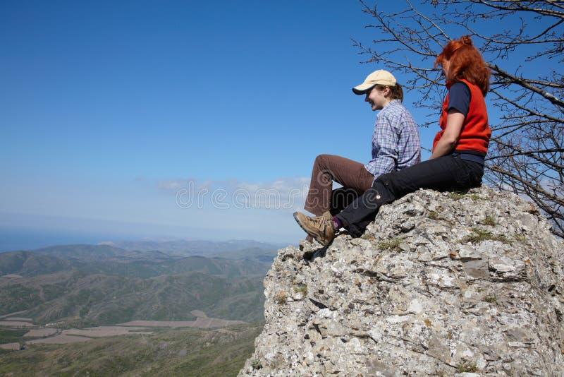 Duas meninas que sentam-se em uma rocha imagens de stock