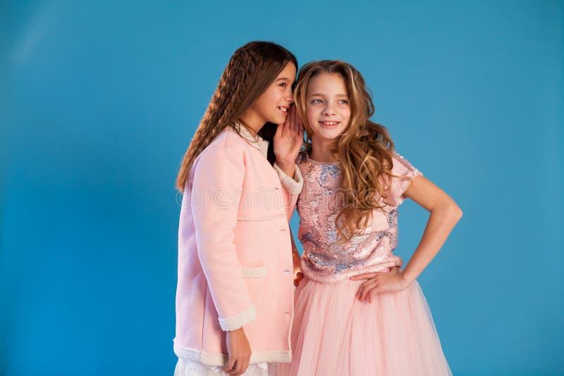 Duas meninas que sussurram entre si a bisbolhetice na orelha imagem de stock