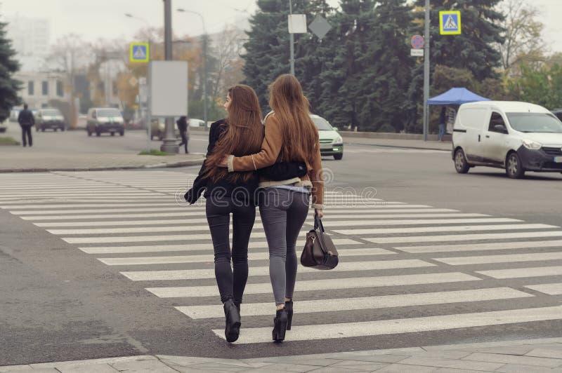 Duas meninas que tentam cruzar a estrada em um cruzamento pedestre fotos de stock royalty free