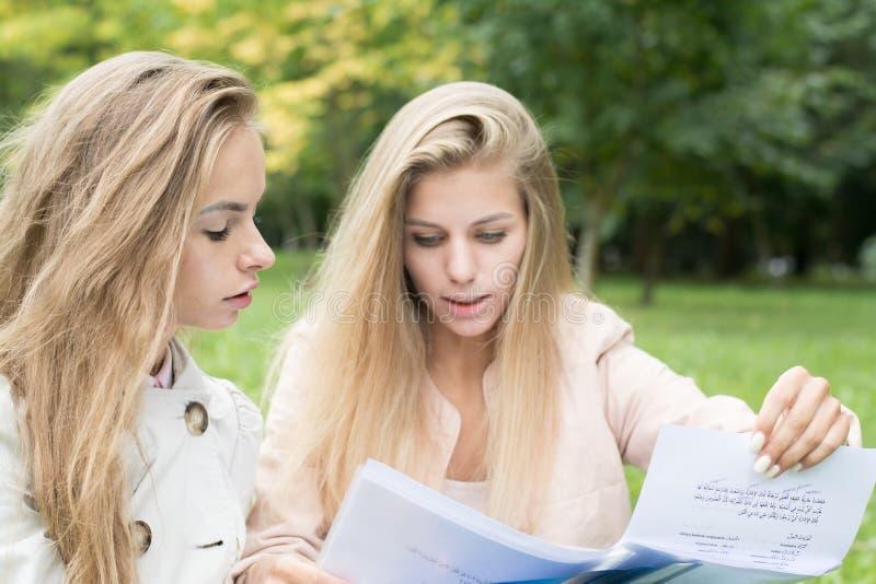 Duas meninas são estudantes fêmeas No verão fazem seus trabalhos de casa na natureza O conceito das turmas escolares na natureza imagem de stock