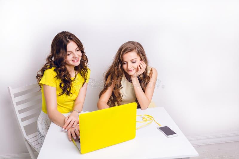 Duas meninas sentam-se atrás de um portátil na caixa amarela Há um smartphone na tabela que carrega através do cabo amarelo Ambas fotos de stock royalty free